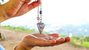 Quartz Crystal Pendulum Hanging over a Hand